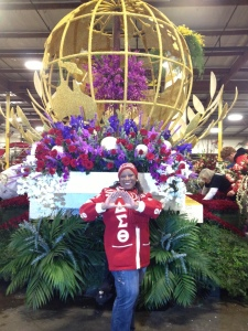 Delta Gail Bowens poses in front of the sorority's Tournament of Roses float.